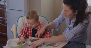 Mother Developing Creativity with Child Drawing with Finger Paints. Indoors stock footage