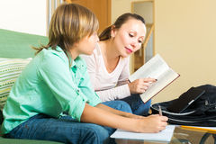 Mother dictating and the son writing. Mother dictating the text and the son writing it in the notebook Stock Photo