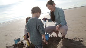 Mother Digging With Children on the Beach stock video