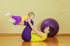 Mother do exercises with her daughter Stock Photo