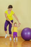 Mother do exercises with her daughter Stock Photos