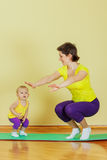Mother do phisical exercises with her daughter Stock Images
