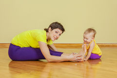 Mother do phisical exercises with her daughter at home Stock Photos