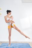 Mother does gymnastics with her baby stock image