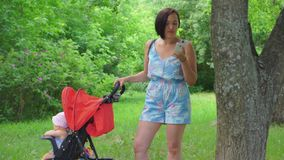 Mother does not look at the child in the stroller, but writes a message in the mobile phone. In nature, the mother does not look at the child in the stroller stock footage