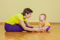 Mother does physical exercises with her daughter at home Royalty Free Stock Photos