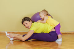 Mother does physical exercises with her daughter. At home Stock Photos