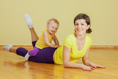 Mother does physical exercises with her daughter. At home Stock Images