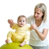 Mother doing gymnastic to kid on fitness ball Royalty Free Stock Image