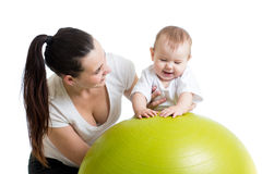 Mother doing gymnastics with baby on fit ball Royalty Free Stock Image