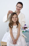 Mother doing her daughter's hair Royalty Free Stock Image