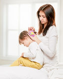 Mother doing her daughter s hair Stock Photo