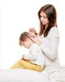 Mother doing her daughter s hair Stock Photos