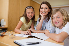 Mother doing homework with children Stock Image