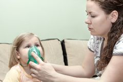 Mother doing inhalation with her little child on sofa at home. Nebulizer device Royalty Free Stock Photos