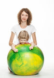 Mother doing sport exercises with daughter. Happy mother doing sport exercises with little daughter on a fitball Stock Image