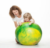 Mother doing sport exercises with little daughter. Happy mother doing sport exercises with little daughter on a fitball Royalty Free Stock Photography