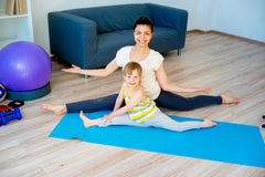 Mother doing yoga with daughter Stock Photo