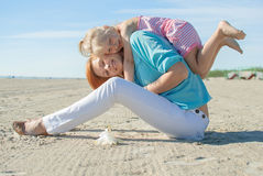 Mother doughter holliday rest. Mother with doughter play sea shore summer Stock Photography