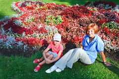 Mother with doughter near flowerbed Royalty Free Stock Photography