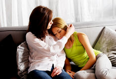 Mother and doughter sitting on sofa. Stock Photography