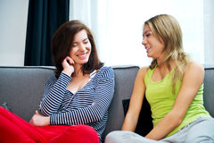 Mother and doughter sitting on sofa. Royalty Free Stock Photography