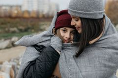 Mother and doughter teenager are walking on the street in warm autumn clothes stock photos