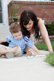 Mother Drawing With Chalk On Sidewalk With Son Stock Photography