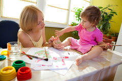 Mother drawing on her daughter Stock Images