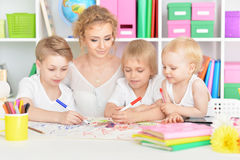 Mother drawing with three cute sons. Portrait of happy mother drawing with three cute sons Stock Images