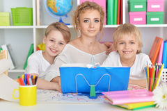 Mother drawing with three cute sons. Portrait of happy mother drawing with three cute sons Stock Photography