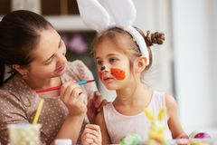 Mother draws on daughter`s face while dyeing the eggs for the Easter table in the cozy light kitchen. royalty free stock photos
