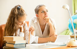 Mother dreaming while daughter doing homework Stock Photo