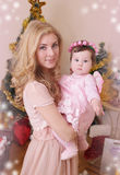 Mother and dressed like angel baby girl at Christmas tree Royalty Free Stock Photography