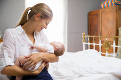 Mother Dressed For Work Holding Baby In Bedroom Stock Photos