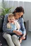 Mother dressing cheerful little baby on sofa. At home royalty free stock photos