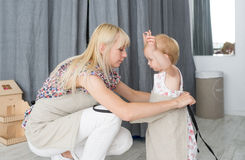 Mother dressing her daughter in the morning for the help with a household royalty free stock photography