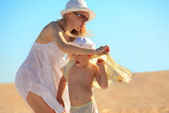 Mother dressing her son Stock Images