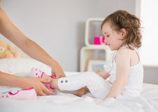 Mother dressing up daughter on bed Royalty Free Stock Photography