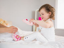 Mother dressing up young daughter on bed Royalty Free Stock Images
