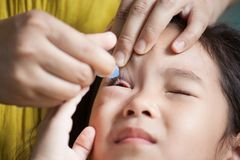 Mother dripping eye medicine in girl eyes Stock Images