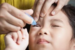 Mother dripping eye medicine in girl eyes Stock Image