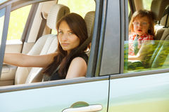 Mother driver and little girl in car safety seat. Stock Photos