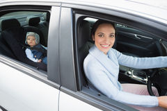 Mother driving with her baby in the car seat Royalty Free Stock Images