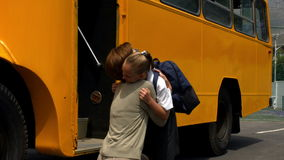 Mother dropping her little girl to school bus stock footage