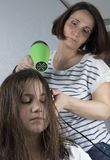 Mother drying hair to her daughter stock photo