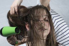Mother drying hair to her daughter stock image