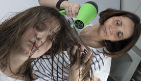 Mother drying hair to her daughter stock images