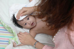 Mother drying her cute little baby's hair Royalty Free Stock Images