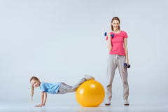 Mother with dumbbells and daughter with fitness ball excising together. Sporty mother with dumbbells and daughter with fitness ball excising together Royalty Free Stock Photos